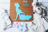 Bilderrahmen der eine schwangere Frau zeigt und das Bild im Bauch der Figur steckt.
