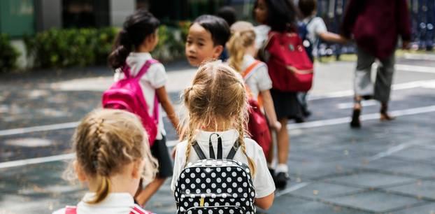 Bayern: Grundschulkinder gehen in einer Zweierreihe Hand in Hand ihrer Lehrerin hinterher über einen Gehweg