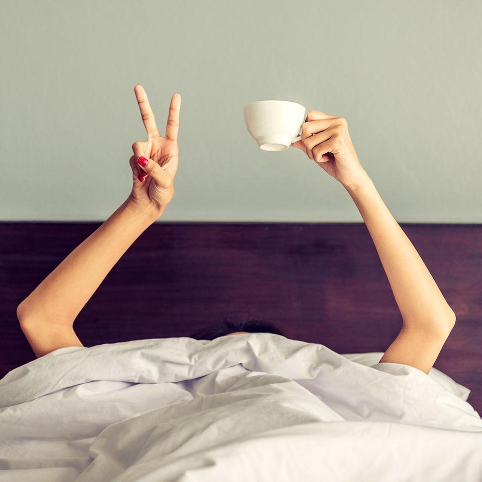 Schlecht geschlafen letzte Nacht? Frau mit Kaffeetasse im Bett (Symbolbild)