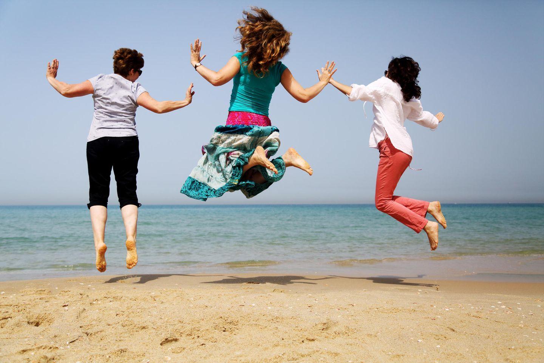Abnehmen ab 50: Drei Frauen am Meer hüpfen in die Luft