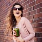junge Frau mit Sonnenbrille und grünem Smoothie lehnt an gemauerter Hauswand