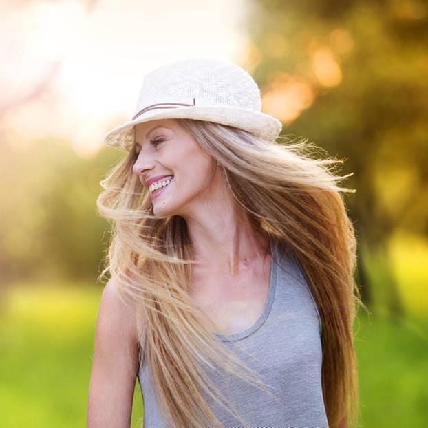 junge Frau mit langen blonden Haaren und Hut auf dem Kopf lachend in der Sonne