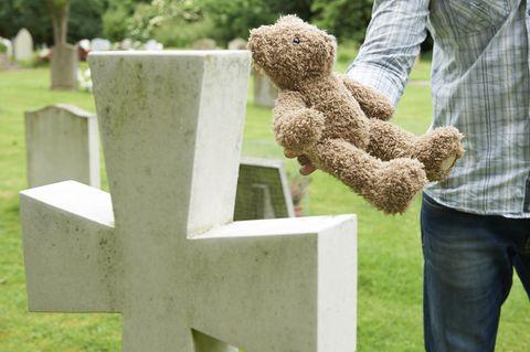 Vater steht mit einem Stoff-Teddy vor einem Grab