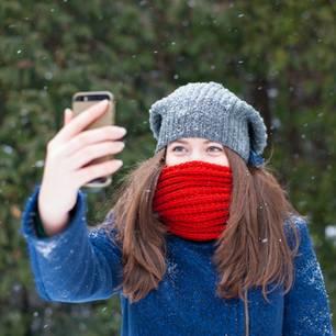 Smartphones bei Kälte: Junge Frau macht ein Selfie im Schnee