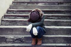 Depression: Eine junge Frau sitzt mit gesenktem Kopf auf einer Steintreppe
