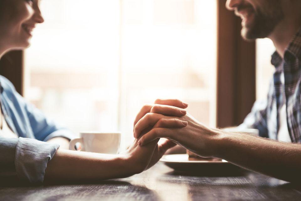 Paar sitzt im Café und hält Händchen
