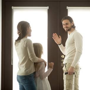 Mutter und Tochter verabschieden Vater an Tür