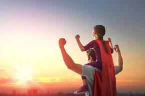 Vater hat Tochter auf Schultern und beide tragen Superheldenkostüme