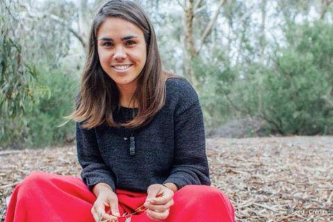 Weltfrauentag: Eine junge Frau sammelt Blätter im Wald