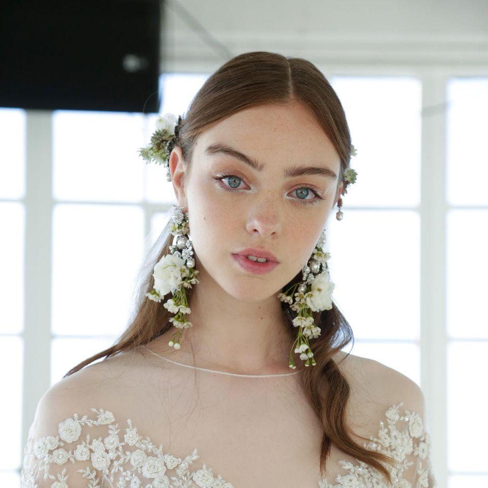 Brautfrisuren: Braut trägt einen Mittelscheitel, zurückgebundene Haare und Blumen im Haar