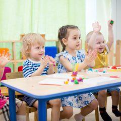 Kinder sitzen in Kita an Tisch, klatschen und melden sich
