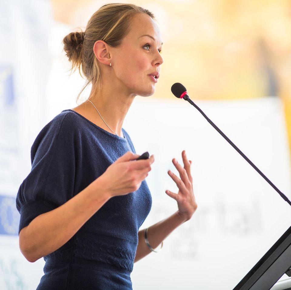 Karriere-Tipps für Frauen: Eine blonde Frau hält eine Rede am Rednerpult mit Mikro