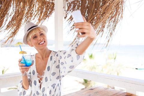 Frau mit Cocktail am Strand.