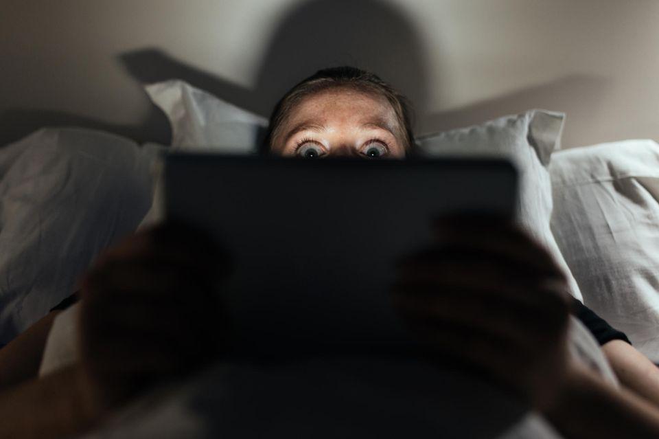 Frau versteckt sich hinter Laptop