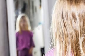 Kind steht vor Spiegel unscharf