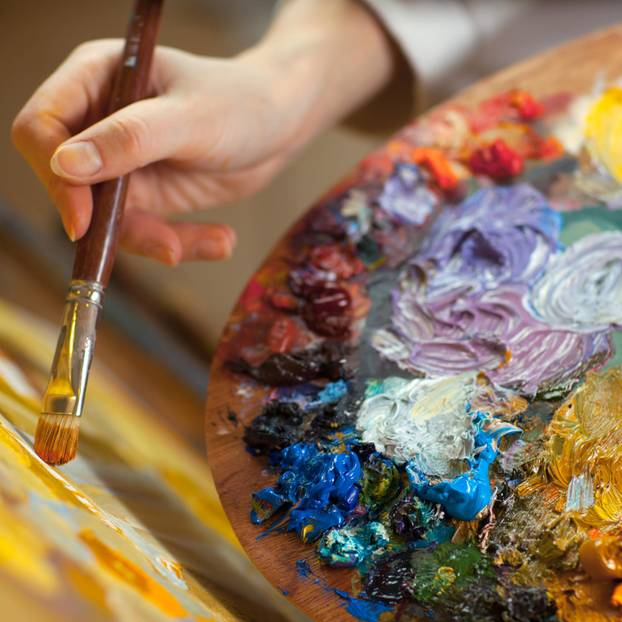 Sexismus? Nahaufnahme einer Malerin vor ihrer Leinwand mit Frabpalette in der Hand