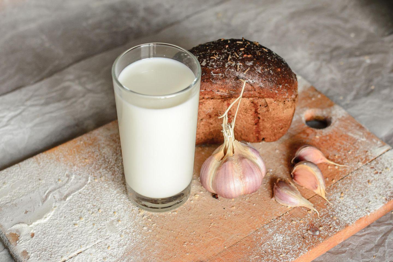 Milch, Knoblauch und Brot auf einem Brett