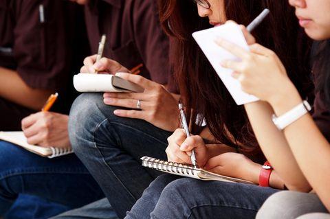 Österreich: Eine Gruppe von Schülern schreibt Notizen auf einen Block