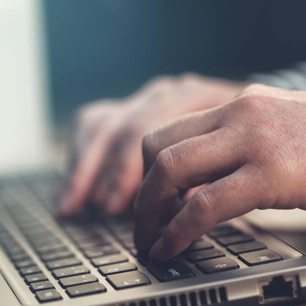 England: Männerhände tippen etwas auf einem Laptop