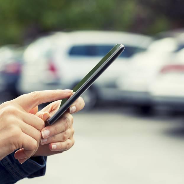 Falschparker-App: Eine Frau mit einem Smartphone auf einem Parkplatz