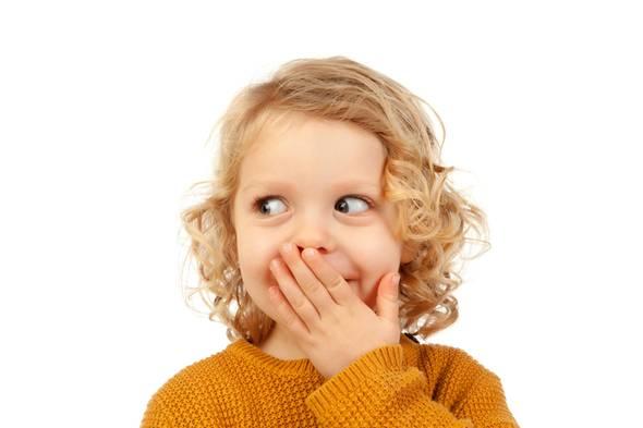 Kind hält sich beschämt und belustigt Hand vor den Mund