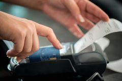Kassenbon aufheben? Hände an einem EC-Gerät, das einen Kassenbon ausdruckt