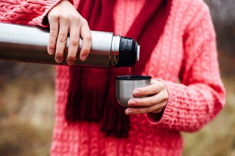 Thermoskanne reinigen: Frau mit Tee