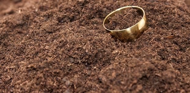 Ein goldener Ring auf einem erdigen Acker