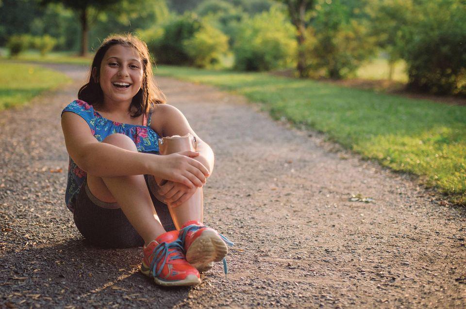 Kind mit Protese sitzt auf Boden und lacht.
