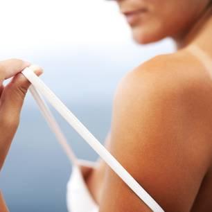 Was hilft gegen Sonnenbrand? Frau zeigt Abdruck auf ihrer Haut unter ihrem Bikiniträger