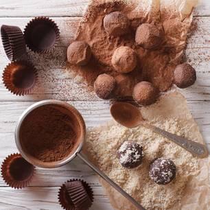 Pralinen selber machen: Trüffel mit Kakaopulver auf Arbeitsplatte