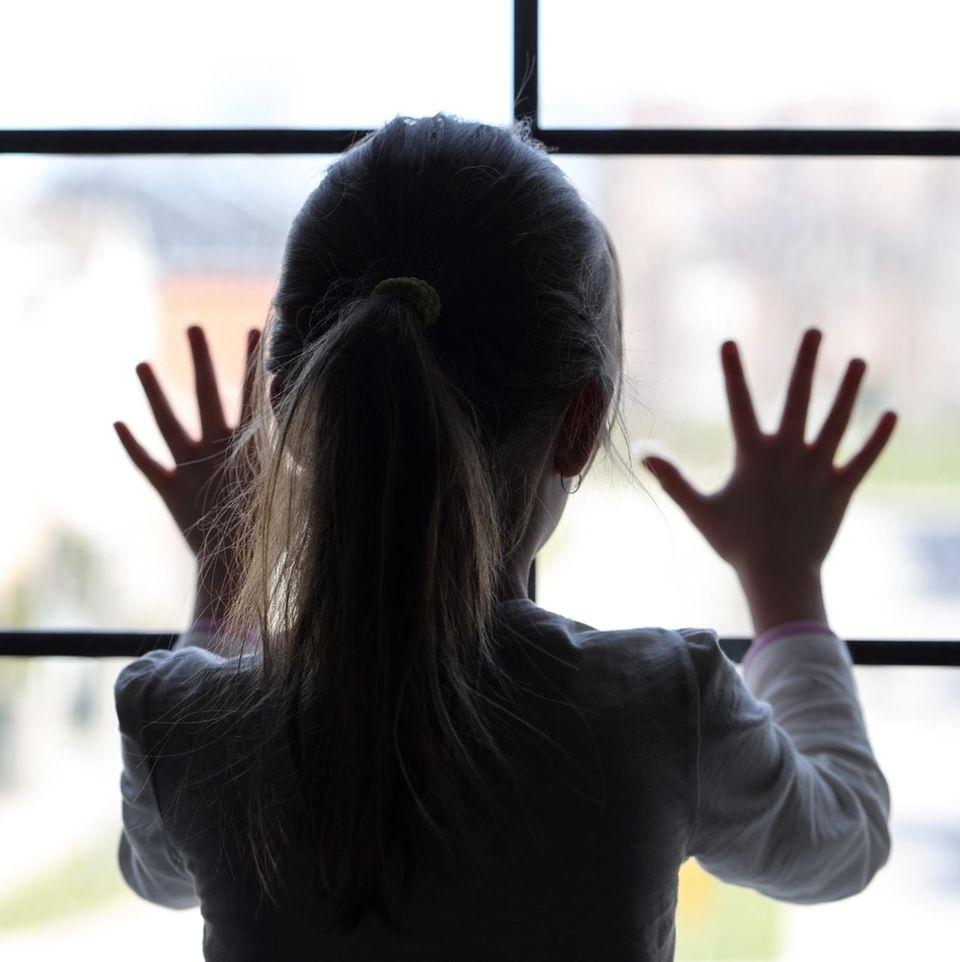 Cottbus: Ein Mädchen steht am Fenster
