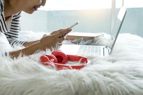 Diese Gewohnheiten machen dumm: Frau mit Smartphone und Laptop im Bett