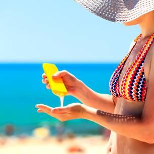 Sonnencreme: Frau dosiert Sonnencreme