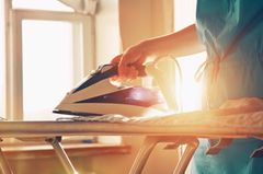 Bügeleisen entkalken: Frau bügelt