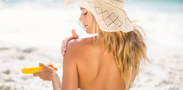 Lichtschutzfaktor: Frau am Strand cremt sich ein