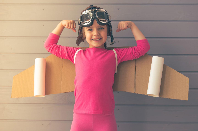 Mädchen in Pilotenkostüm macht starke Pose