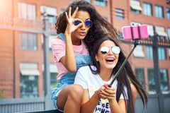 Instagram: Zwei junge Frauen fotografieren sich mit einem Selfie-Stick
