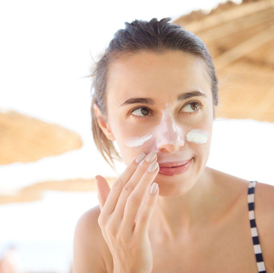 Sonnenbrand im Gesicht: Frau cremt sich am Strand das Gesicht ein
