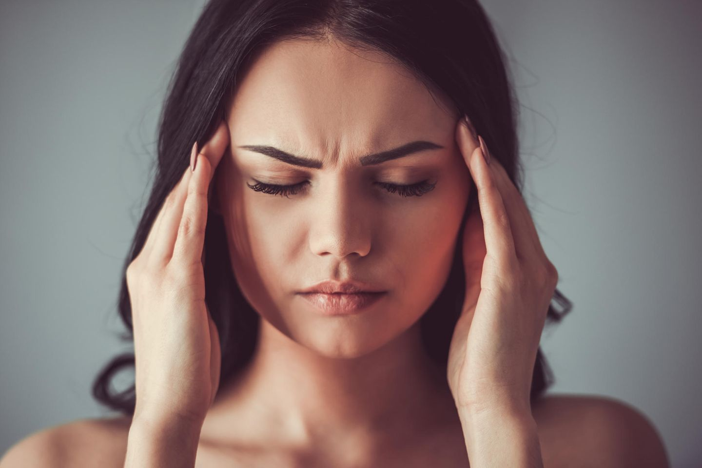 Headache: Woman with a contorted face in pain holds her hands to her forehead
