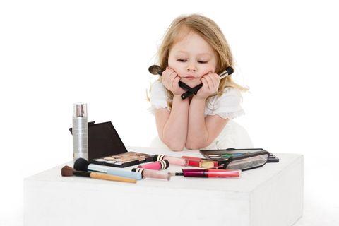 Kleines Mädchen sitzt traurig über Schminke