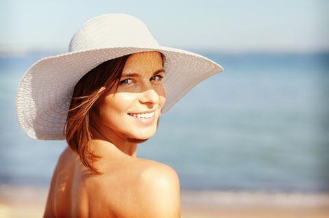 LSF 50: Frau mit Hut am Strand