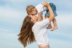 Fröhliche Mutter hebt Jungen in die Luft