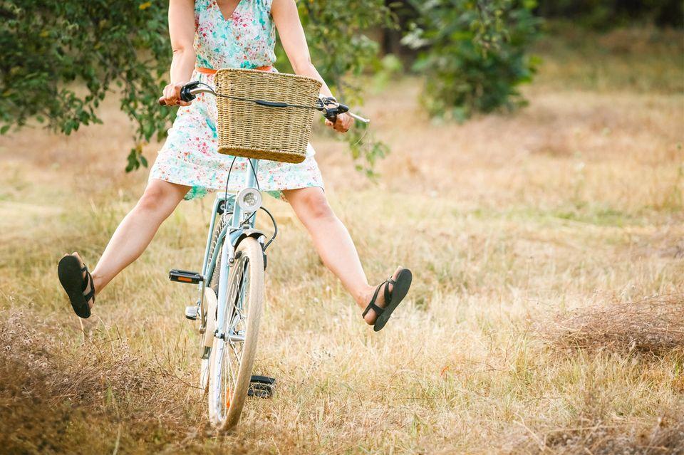 Frau fährt fröhlich und frei auf Rad