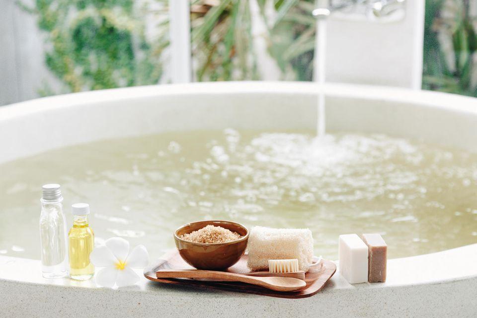 Badewanne läuft ein, Badezusätze und Seifen stehen am Rand