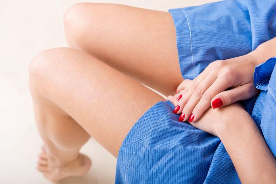 Patientin beim Frauenarzt sitzt angespannt mit den Hände im Schoß auf dem Stuhl