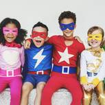 Kinder unterschiedlichen Alters in Superhelden-Kostümen beim Rumalbern
