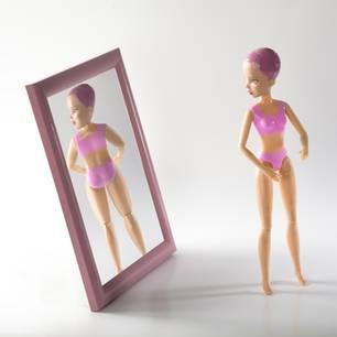 Barbie steht vor dem Spiegel