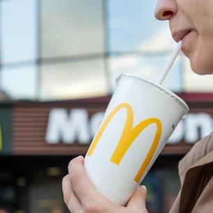 Plastikmüll: Frau trinkt durch einen Strohhalm aus McDonald's-Becher