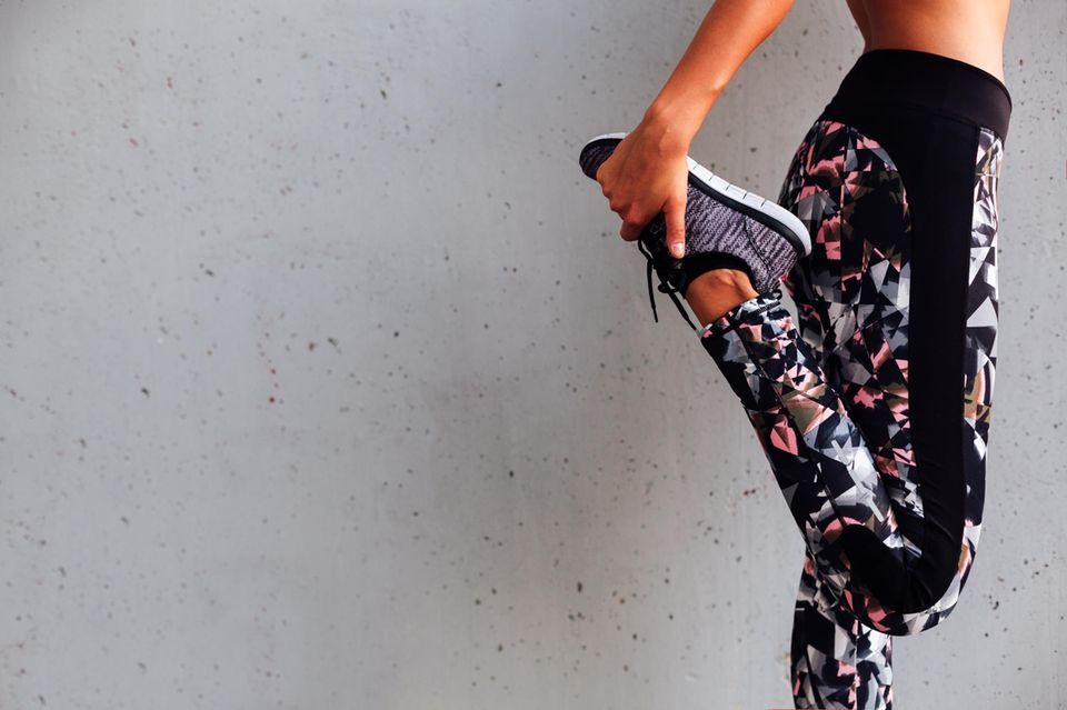 Diese Übungen sorgen für straffe Beine: Frau stretcht sich an grauer Wand
